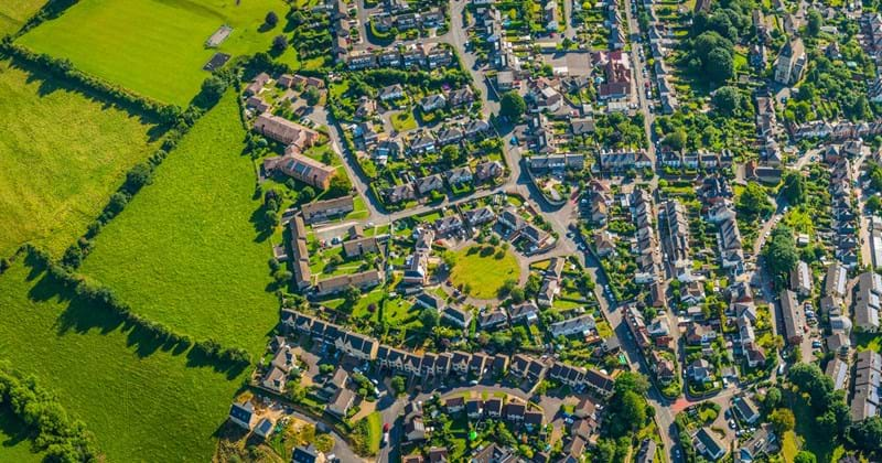 Birdseye view of suburban residential community with houses, streets, trees and park spaces